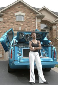 Sharon with her customized Cadillac in front of her House when the going was Rosy.